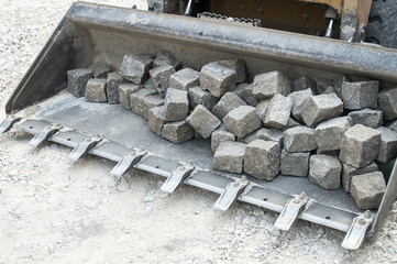 Bulldozer front loader closeup full with granite vintage street stone paves