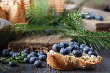 Fresh bread with blueberry jam and fruits on a rustic table