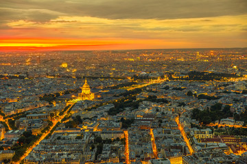 Paris urban skyline cityscape. Aerial view of national residence of the Invalids palace on orange sunset with night street light from panoramic terrace of Tour Montparnasse. European capital of France Fotomurales