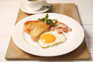 Fried egg with bacon and toasted bread on plate served for breakfast