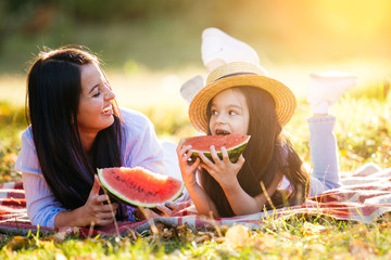 young mom with daughter eat watermelon in park