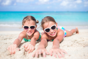 Close up little girls on sandy beach. Happy kids lying on warm white sandy beach