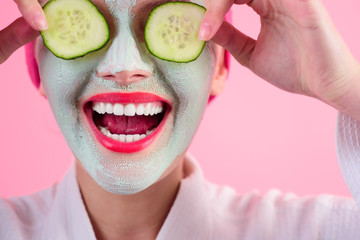 Close up portrait of woman with facial cosmetical mask and cucumber slice on eyes. Cosmetic...