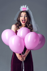 excited future bride in veil for bachelorette party holding bunch of pink air balloons isolated on grey