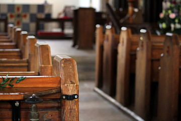 Close up of the end of a row of wooden pews in a traditional stone built church, with the altar in out of focus background