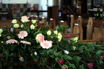 Beautiful display of pink and yellow flowers, behind the rows of wooden pews in a traditional stone built church, with the altar in out of focus background