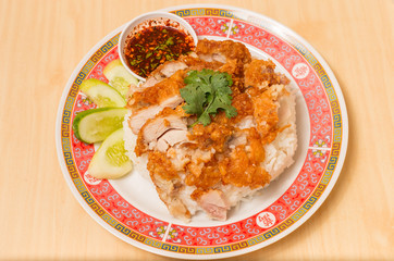 Fried chicken place on top the rice with cucumbers and sauce.