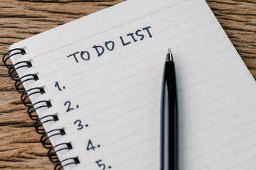 To Do List concept, pen on white paper note pad with handwritten headline as To Do List and numbers listed on wood table in soft tone, writing business project with tasks priority