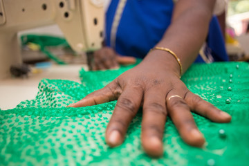 Tailor sewing a green piece of cloth