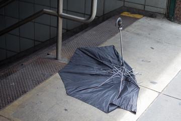 Broken umbrella outside subway entrance
