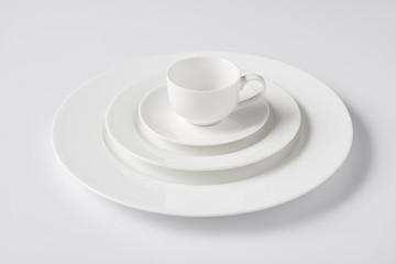 selective focus of cup on stack of different plates on white table