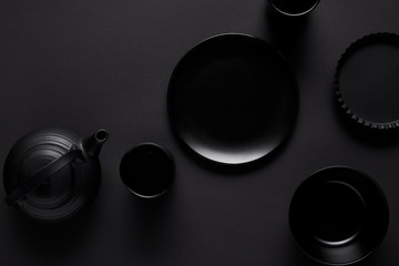 top view of black teapot, plate, bowl, cups and baking dish on black table