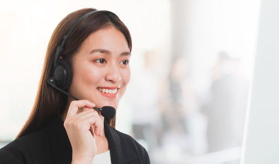 Portrait of Asian beautiful smiling woman customer support phone operator in office space background and copy space.Concept call center job service.