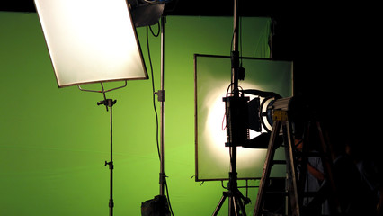 Big studio lighting kit 5000 watt with soft box on tripod and professional green screen background chroma key post production technique shooting or filming for movie or video commercial set up.