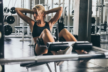 Attractive young woman doing sit up exercise with machine at the gym.