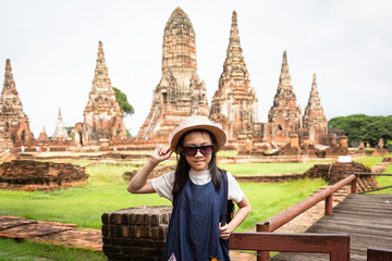Cute happy smiling tourist girl,relaxing enjoying travelling at Wat Chaiwatthanaram is a Buddhist temple in the city of Ayutthaya Historical Park,Thailand, summer vacation,travel concept.