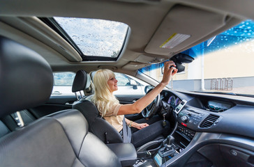 Blonde woman in modern car.