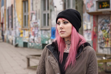 young alternative pierced and tattooed woman in front of graffiti covered building