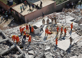 Rescue workers look for survivors amidst the rubble at the site of a collapsed residential building at Shah Beri village in Greater Noida