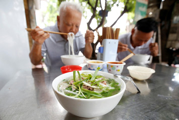 "Poeple eat the Vietnamese traditional beef noodle ""Pho"" at a breakfast restaurant in Hanoi"