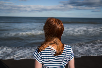The young girl looking at the sea