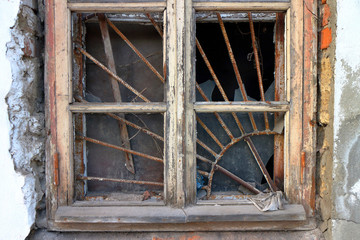 Old wooden window with a lattice and broken glass