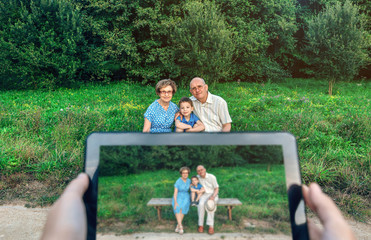 Grandparents and grandson posing while someone takes a picture with the tablet. Selective focus on family in background