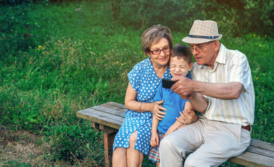 Grandfather taking selfie with grandmother and grandson sitting on a bench