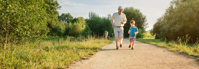 Front view of senior man with hat and happy child running on a nature path. Two different generations concept. Wall mural
