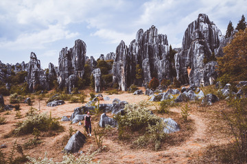 Woman tourist in stone forest, rock formations in Yunnan, China