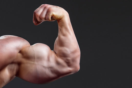 bodybuilding naked male arm with biceps on grey background. muscular man's hand shows your business on a dark grey background, biceps close-up