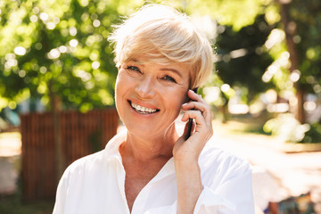 Smiling mature woman talking on mobile phone