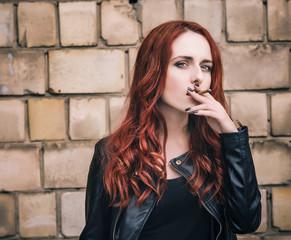 Beautiful girl smokes while waiting in the street.