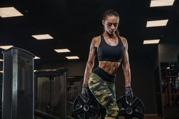 Concept-strength, beauty, training, diet, sports nutrition. A young brunette woman, an athlete bodybuilder does exercises in a modern gymsportswear, camouflage.