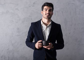 A happy handsome young businessman in a black suit holding a black mug in front of a grey wall in a studio.