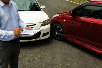 The insurance agent examining car after accident on the road. Insurance claim concept .