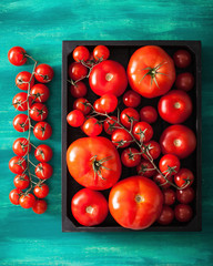 assorted tomatoes in wooden box