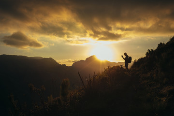 Hiker taking pictures of mountain valley at sunset