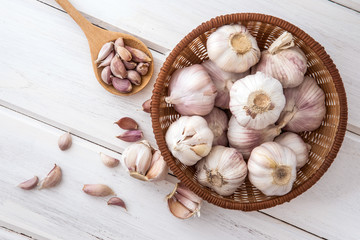 Close up group of garlic on a white wooden table board , top view or overhead shot with copy space