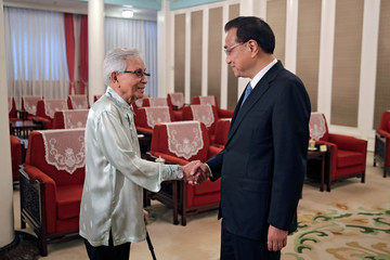 Malaysia's new government advisor Daim Zainuddin shakes hands with Chinese Premier Li Keqiang before proceeding to their meeting at the Zhongnanhai Leadership Compound in Beijing