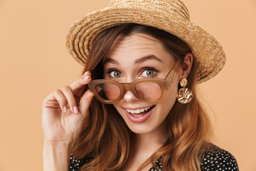 Portrait of cheerful young woman 20s wearing straw hat and sunglasses looking at camera, isolated over beige background