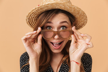 Portrait of summer surprised woman 20s wearing straw hat touching sunglasses and looking at camera, isolated over beige background