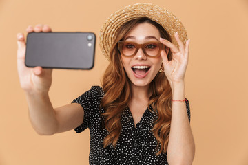 Portrait of cheerful pretty woman wearing straw hat and sunglasses laughing and taking selfie photo on smartphone, isolated over beige background