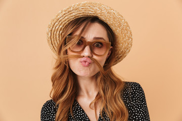 Portrait of amusing funny woman 20s wearing straw hat and sunglasses fooling around and putting hair like mustache, isolated over beige background