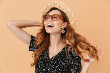 Portrait of cheerful beautiful woman with beautiful hair wearing straw hat and sunglasses laughing and looking aside, isolated over beige background