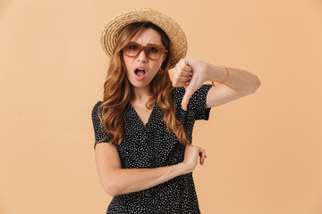Portrait of frustrated displeased woman 20s wearing straw hat and sunglasses showing thumb down, isolated over beige background
