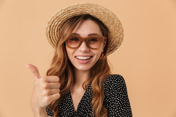 Portrait of lovely woman 20s wearing straw hat and sunglasses smiling and showing thumb up, isolated over beige background