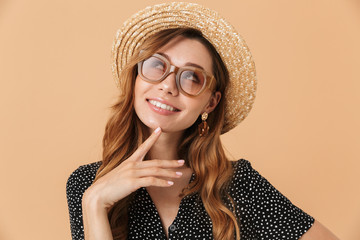 Portrait of gorgeous stylish woman wearing straw hat and sunglasses smiling and looking upward, isolated over beige background