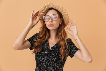 Portrait of gorgeous stylish woman wearing sunglasses touching beautiful straw hat on head, isolated over beige background