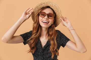 Photo of elegant european woman wearing sunglasses touching beautiful straw hat on head, isolated over beige background